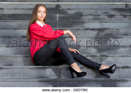 Young woman wearing a red top, black jeans and high heels posing while sitting on stairs - Stock Photo