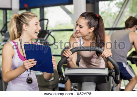 Trainer woman talking with a woman doing exercise bike - Stock Photo