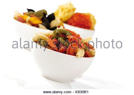 Different types of coloured pasta in bowls - Stock Photo