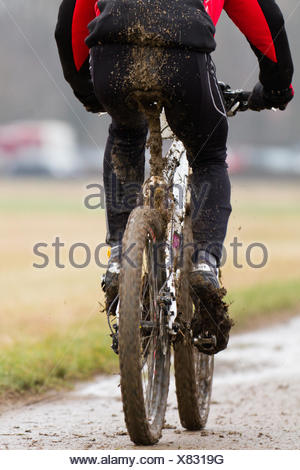 on the move,mountain biker,bicycle tour,mud - Stock Photo