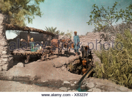 Men clean out the stagnant water with a water-scoop wheel. - Stock Photo