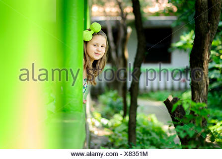 Girl (6-7) playing hide-and-seek - Stock Photo
