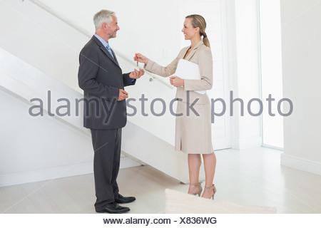 Smiling estate agent handing over keys to customer - Stock Photo