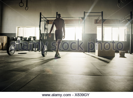 Young man preparing for exercise bar in gymnasium - Stock Photo