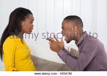 Angry Young African Man Screaming At Woman - Stock Photo