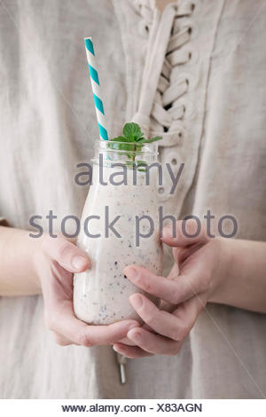 Bottle of smoothie with chia seeds, blueberries, mint leaves and retro striped cocktail tube in female hands. Woman in white linen dress. Healthy eati - Stock Photo