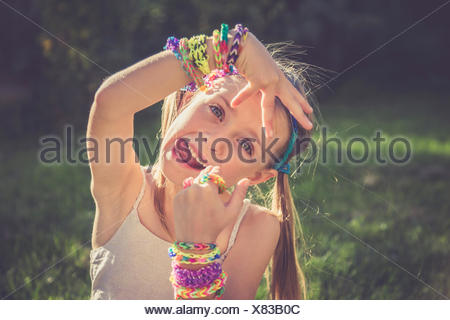 Portrait of little girl with outstretched tongue showing her loom bracelets and rings - Stock Photo