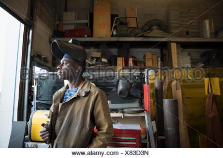 Pensive welder wearing protective workwear looking away in workshop - Stock Photo