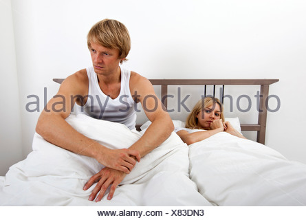 Angry man sitting on bed with woman in house - Stock Photo