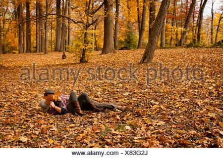 Young couple play fighting in autumn forest - Stock Photo