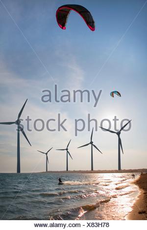 Croatia, Zadar, Kitesurfer jumping in front of wind turbine at sunset - Stock Photo