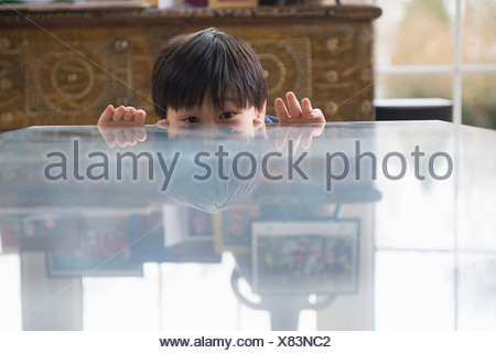 Portrait of boy peeking over dining room table - Stock Photo