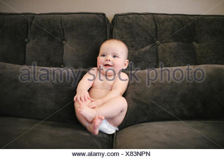 A baby sitting propped up on a sofa wearing a diaper. - Stock Photo
