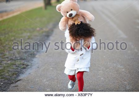 Front view of girl carrying soft toy on shoulders looking down - Stock Photo
