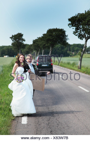 Wedding couple hitch hiking on road - Stock Photo