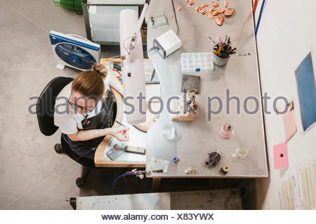 Overhead view of female jeweller at workbench - Stock Photo