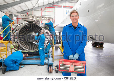 Team Of Aero Engineers Working On Aircraft In Hangar - Stock Photo
