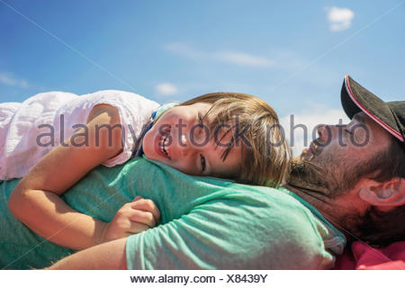 Smiling girl lying on her father's chest - Stock Photo