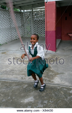Girl wearing school uniform playing with a skipping rope at an Ursuline convent and orphanage in Georgetown, Guyana, South Amer - Stock Photo