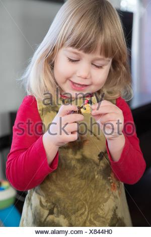 three years old little girl child blonde bang hair with red shirt green dress playing and talking to little dolls in her hands. - Stock Photo