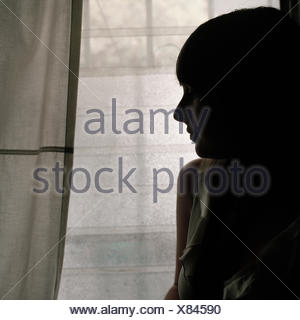 A woman standing next to a window - Stock Photo