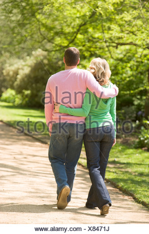 Couple walking on path arm in arm - Stock Photo