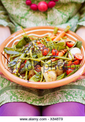 Woman holding plate of vegetable salad - Stock Photo