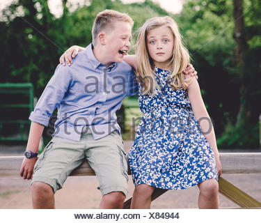 Boy and girl sitting on wooden gate with their arms around each other - Stock Photo