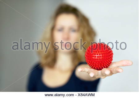 Young woman holding a spiky massage ball in her outstretched hand - Stock Photo