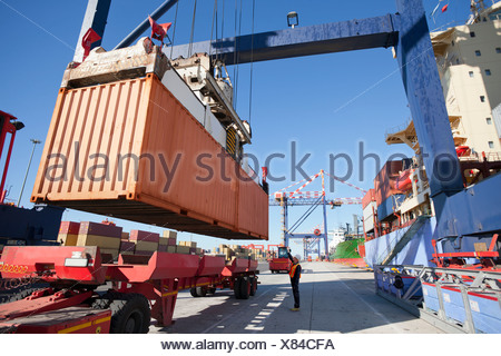 Crane unloading container ship at commercial dock - Stock Photo