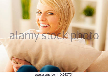 Beautiful and smiling woman embracing pillow Debica, Poland - Stock Photo
