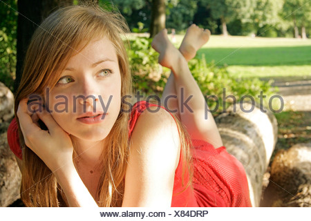 young woman lying on tree trunk, Germany - Stock Photo