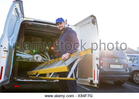 Portrait of handyman loading a ladder - Stock Photo