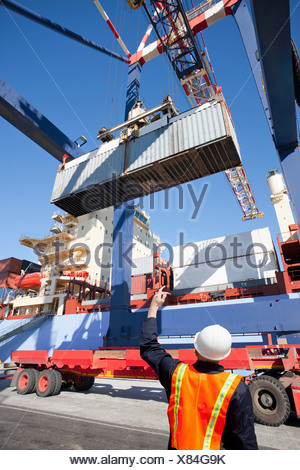Worker guiding crane with cargo container at commercial dock - Stock Photo