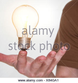 Man holding a lightbulb on his finger - Stock Photo