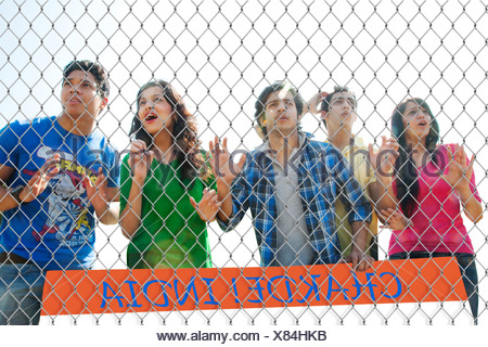 Youngsters watching a match through a wire mesh - Stock Photo