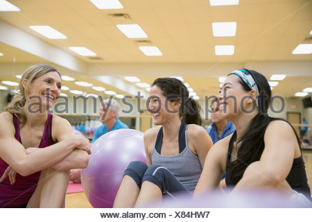 Smiling women talking in exercise class - Stock Photo