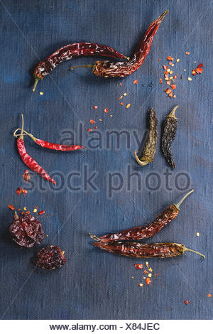 Assortment of dryed whole and flakes red hot chili peppers over dark blue canvas as background - Stock Photo