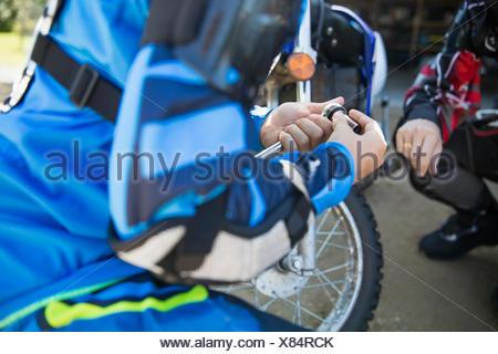 Girl using socket wrench, fixing motorbike - Stock Photo