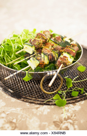 pork kebabs on bed of chopped parsley and garlic - Stock Photo