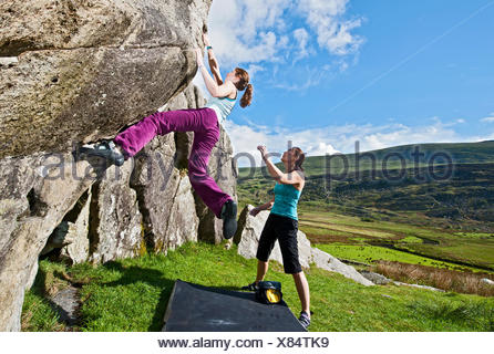Female Climber bouldering on RAC Boulders, spotted by another climber, Snowdonia, North Wales, UK - Stock Photo