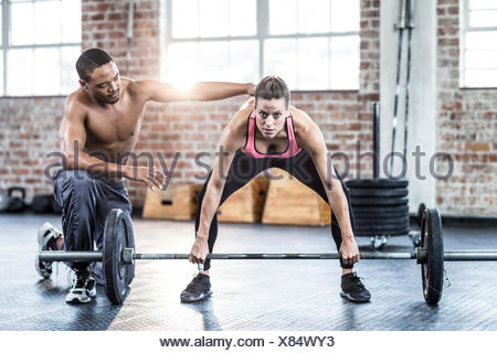 Trainer helping woman with lifting barbell - Stock Photo