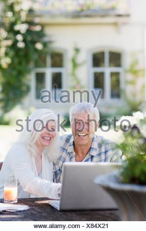 Senior couple using laptop at table in garden - Stock Photo