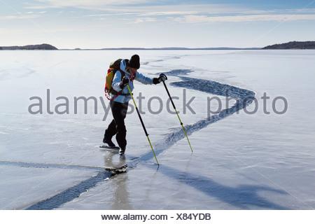 Person skating at frozen sea - Stock Photo