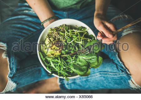 Green vegan breakfast meal in bowl with spinach, arugula, avocado, seeds and sprouts. Girl in jeans holding fork with knees and hands visible, top vie - Stock Photo