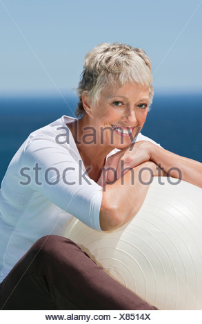 Smiling senior woman leaning on fitness ball - Stock Photo