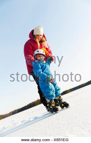 Sweden, Sodermanland, Jarna, Mother teaching son (2-3) ice skating on frozen lake - Stock Photo