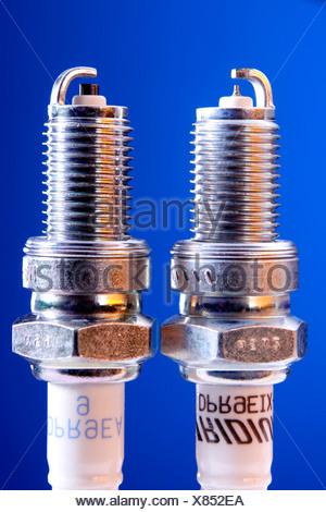 Comparison of iridium spark plug and standard spark plug - Stock Photo