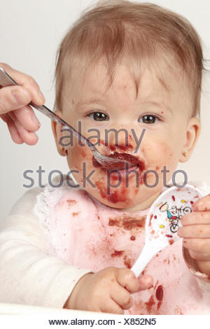 Portrait of an eight-months-old baby girl being fed pulpy fruit by her mother. - Stock Photo
