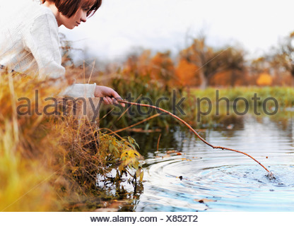 A woman poking at the water with a stick - Stock Photo